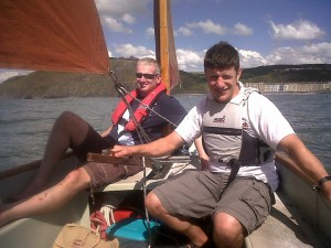 Two men sailing underneath Constitution Hill (Aberystwyth)